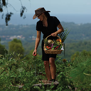 Woman with basket of fruit and veggies in garden
