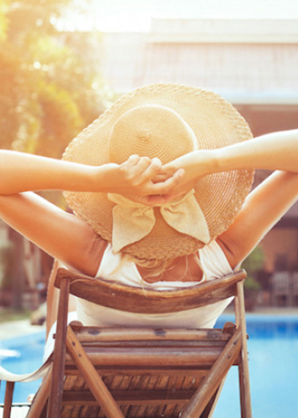 Woman relaxing at pool wearing a sun hat
